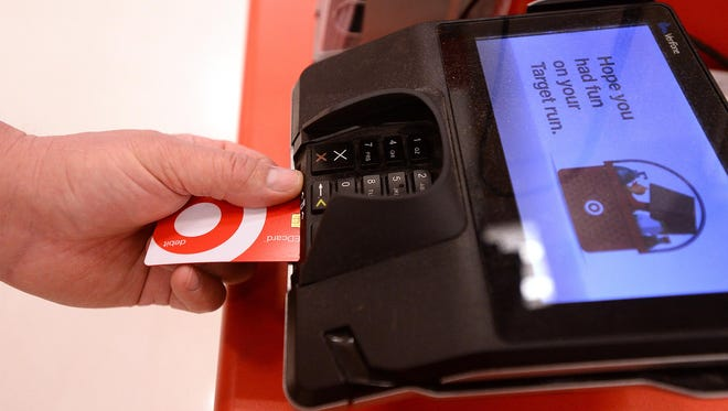 Bryan Daul, store team leader at Target, demonstrates the use of a smart debit card, which uses an integrated chip embedded in the card instead of a magnetic strip to process transactions, Monday afternoon at a Target checkout counter. The use of smart credit and debit cards are becoming more prevalent with retailers.