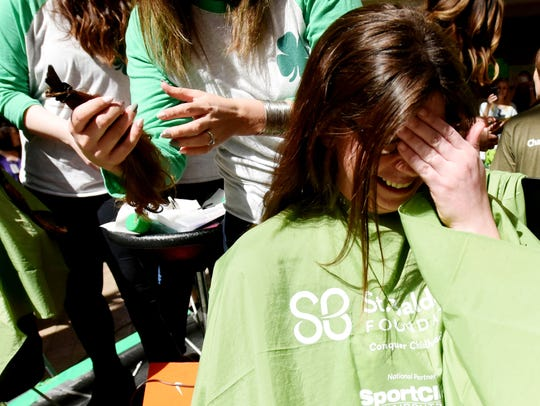 Taylor Thompson reacts to getting her hair cut during the annual St. Baldrick's Foundation Geaux Bald event Friday at LSU Health Shreveport. The event raises funds for childhood cancer research.