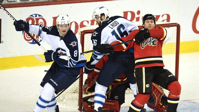 Calgary Flames defenseman Dennis Wideman (6) battles for position with Winnipeg Jets defenseman Jacob Trouba (8) during the second period at Scotiabank Saddledome.