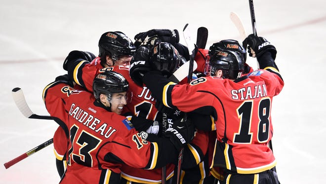 Calgary Flames left wing Johnny Gaudreau (13) and team celebrate the win over the Anaheim Ducks in overtime in game three of the second round of the 2015 Stanley Cup Playoffs at Scotiabank Saddledome.