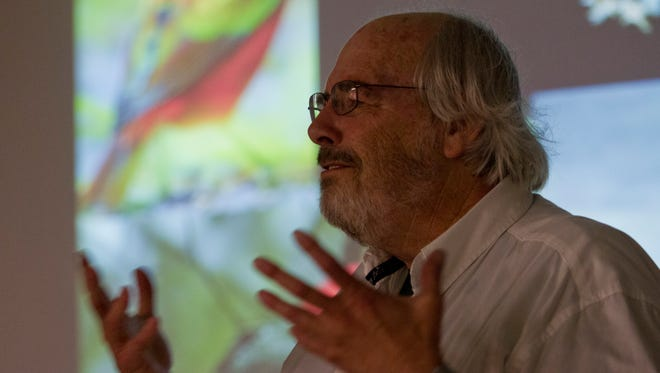 """World-renowned paleontologist Jack Horner speaks before a standing-room only crowd at the Great Falls Public Library on Thursday night. Horner's presentation focused on dinosaur """"accoutrements"""" — spikes, plates, feathers, horns — and what uses they served."""