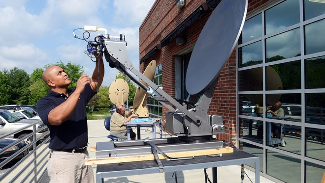 Lou Johnson, a Service Tech Operator at AVL Technologies, works on a satellite dish that was sent back for service outside the facility in Woodfin.
