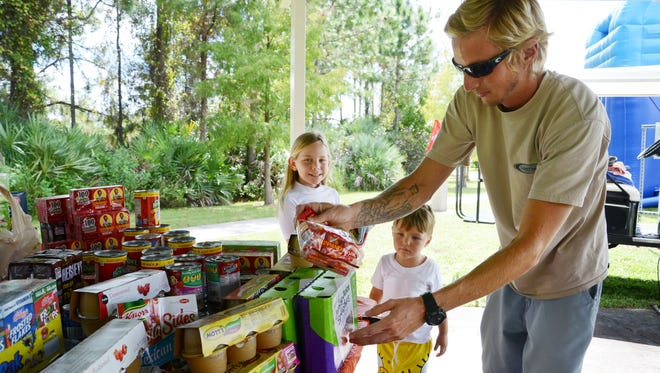 Preston Reed and his children Miya, 8, and Owen, 3,  drop off food items for the hungry at Addison Gaffney's birthday party Saturday.  Gaffney asked all her friends to bring food items for the Children's Hunger Project instead of gifts.