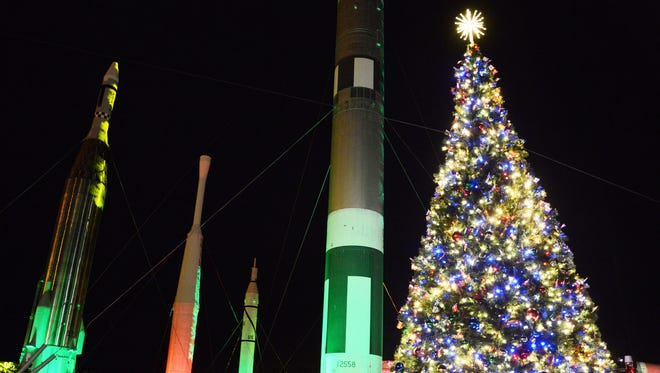 """The rockets in the Rocket Garden are all illuminated in colored lights during a past """"Holidays In Space"""" at Kennedy Space Center Visitor Complex."""