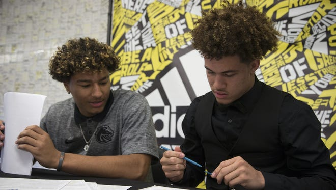 Byron Murphy (right) signs his national letter of intent, February 3, 2016, at Saguaro High School, 6250 North 82nd Street, Scottsdale. Murphy is going to attend Washington. Looking on is Julian Carter (left), who is attending Boise State.