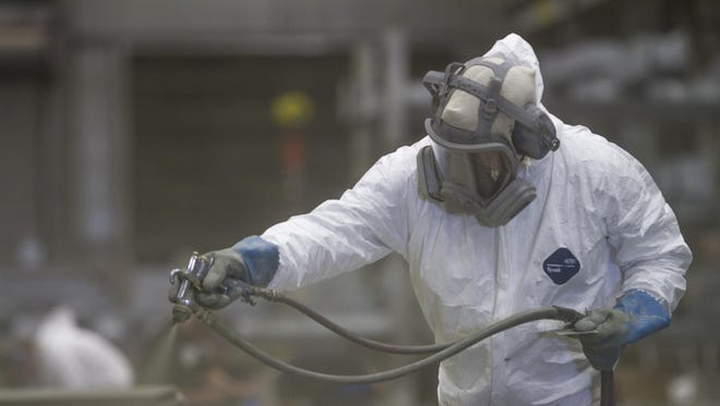 An employee of ADF International applies an industrial coating to a steel beam in the company's paint facility in Great Falls in June.