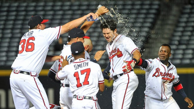 Braves third baseman Chase d'Arnaud (second from right) celebrates with teammates after driving in the game-winning run on a single to center field in which Jace Peterson scored during the 13th inning Wednesday in Atlanta. The Braves won 9-8.