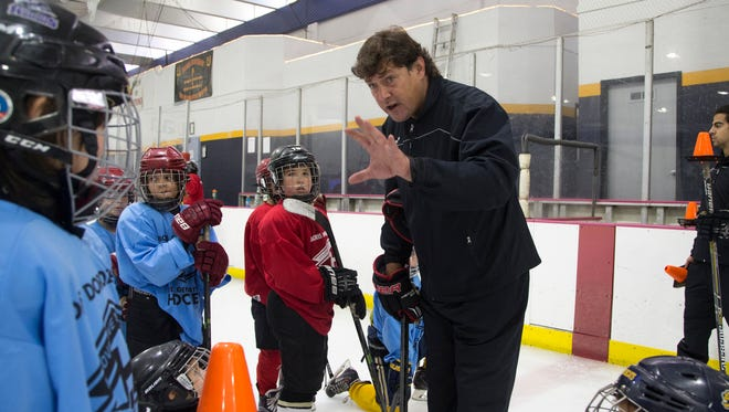 Boris Dorozhenko (center) works with students during his Next Generation Hockey School at the Arcadia Ice Arena.
