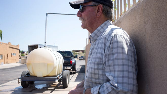 Cave Creek resident JD Smith waits for his 1,000 gallon tank to fill on Aug. 24, 2016, at a water station in Carefree. Smith, who raises Arabian horses at his Cave Creek ranch, makes the 22-mile round trip to the station up to three times a day.