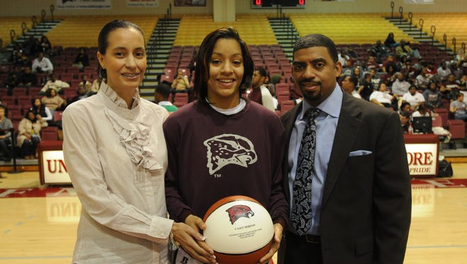Casey Morton, UMES basketball player, is presented with a commemorative basketball after scoring her 1,000th career point in 2011. The Mardela High School graduate is flanked her mother, Dana VanLandingham, on her left, and head coach Fred Batchelor on her right. Morton was named as an assistant coach on Batchelor's staff on Nov. 10, 2016.