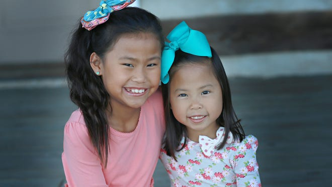Ellianna Maneage, left, and her half-sister Kinley Galbierz, right found out they were related years after being adopted by families in the same Missouri town.