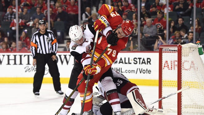 Calgary Flames left wing Michael Ferland (79) battles with Arizona Coyotes defenseman Connor Murphy (5) at Scotiabank Saddledome. Flames won 4-2.