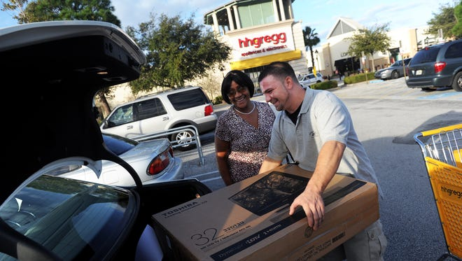 Hhgregg employee Jeremiah Turner loads a customer's television on Nov. 25, 2011, at the Treasure Coast Square mall in Jensen Beach. The store and 87 others nationwide will be closing, the company announced Thursday, March 2, 2017.