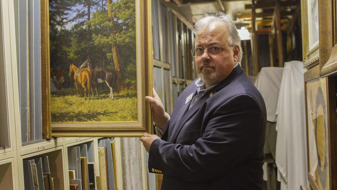 Bruce Wittenberg, director of the Montana Historical Society, pulls out an unexpected treasure in 2015 while browsing through some of the many works of fine art in storage at the museum.
