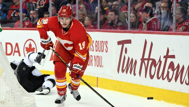 Calgary Flames left wing Matthew Tkachuk (19) chases after the puck after a collision with Los Angeles Kings defenseman Drew Doughty (8) (not pictured) during the first period at Scotiabank Saddledome.