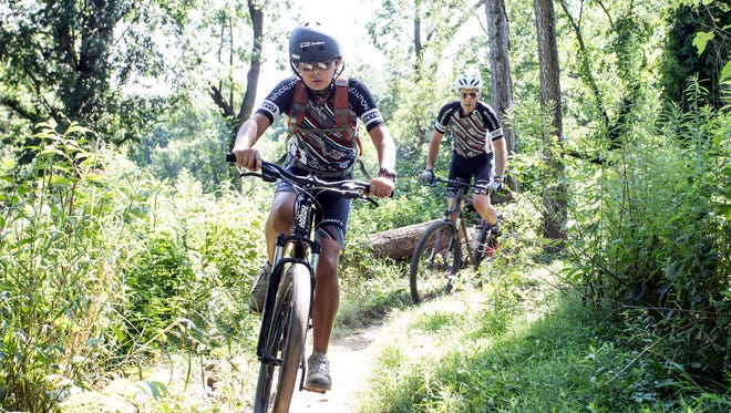 Revolution Devo Cycling team member Jon Adamczyk rides along a narrow path under the guidance of coach Mike Seiler during a training exercise in Seneca Park. 7/9/17