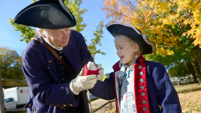 Stephen Pancoe, left, portraying an 18th century magistrate, helps 5-year-old Tessa Scarpato find her hand as she puts on period era clothing during her visit to the Articles of Confederation Day celebration at the Colonial Courthouse on Saturday, Nov. 4, 2017.