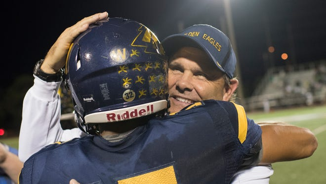 Naples Head coach Bill Kramer hugs quarterback Jordan Persad-Tirone after the team beat Fort Myers in the 6A regional final game at Naples High Friday night, November 24, 2017.