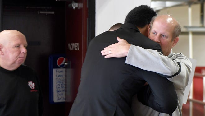 Andrew Leota hugs head coach David Burdette after a ceremony celebrating his signing with Northwestern University to play football at Asheville High School on Tuesday, Dec. 19, 2017.