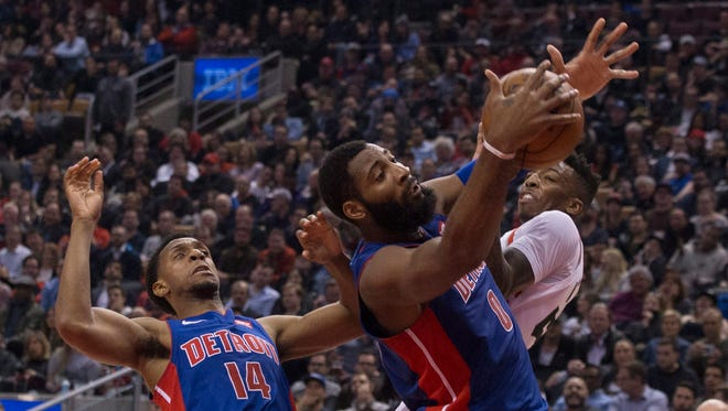 Andre Drummond claims a loose ball in front of the Raptors' Delon Wright during the first half in Toronto on Monday.