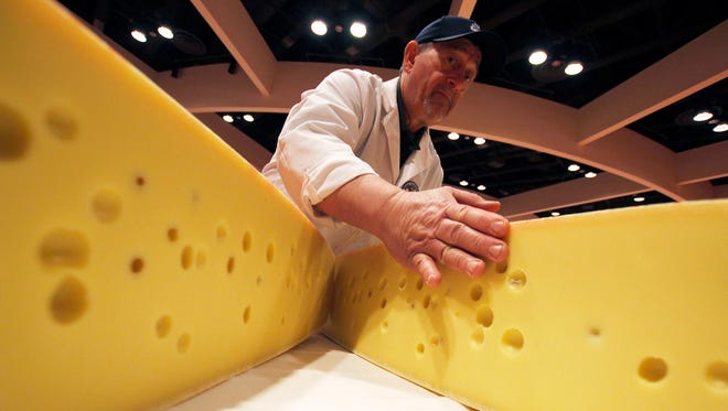 Volunteer Gordy Bergemann opens a round of swiss cheese during the World Championship Cheese Contest.