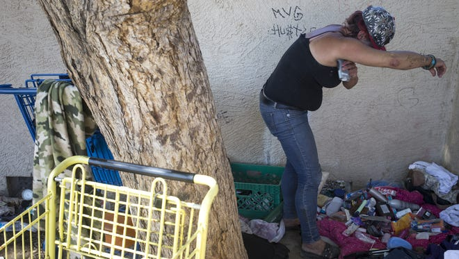 Jenna Ware, 45, puts on deodorant on June 27, 2018, in the alley she lives in behind Bonsall Park, 59th Avenue and Bethany Home Roads, Glendale.