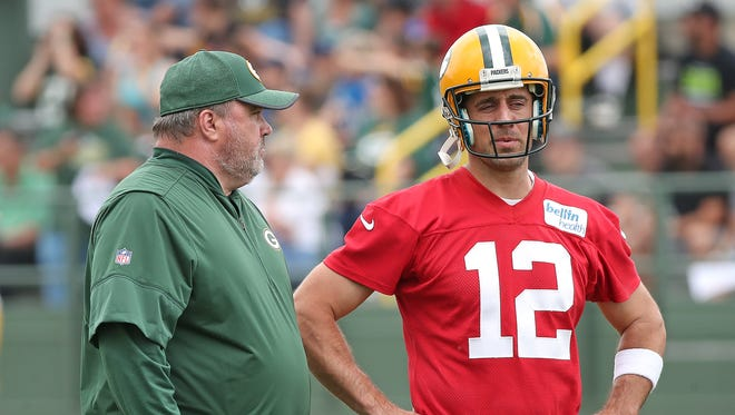 Green Bay Packers quarterback Aaron Rodgers (12) talks with coach Mike McCarthy during OTAs practice on May 31, 2018, at Ray Nitschke Field.