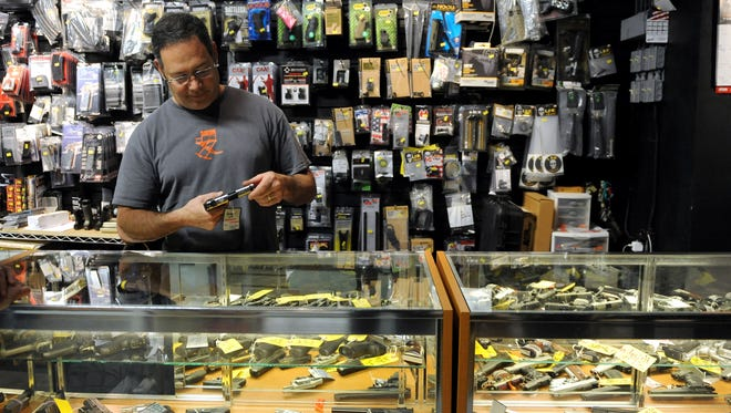 Jeff Stucker examines a hand gun at a display case at On Target Shooting Range Friday. Several gun bills are making their way through the General Assembly this year, including one that would eliminate pistol purchase permits and another that would create an unrestricted concealed carry permit. Stucker said he would be interested in the special permit, if requirements are in place for continuing training and practice.