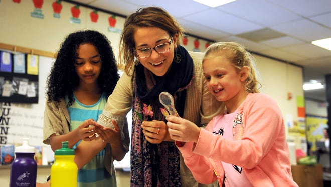Alex Lines, center, a student of Warren Wilson College and EcoTeam member, examines the parts of a flower with Haw Creek Elementary students Amaya Casiano, left, and Kadence Gates Tuesday morning.