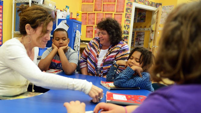 Francine Delany New School For Children operations manager Buffy Fowler works with second-graders during a reading lesson last week with teacher Elana Froehlich, left.