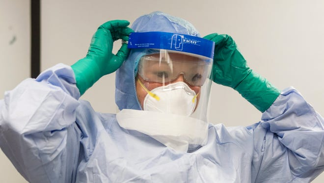 A healthcare professional adjusts her mask during a demonstration of Personal Protective Equipment procedures at Toronto Western Hospital.