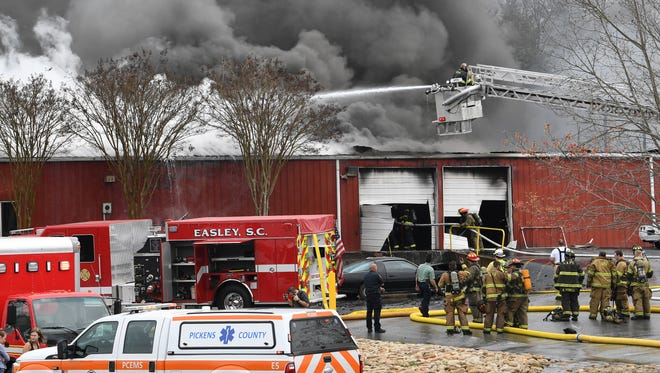 Firemen work at the fire at Ethan's Shop in on State Highway 8 in Easley on Tuesday.