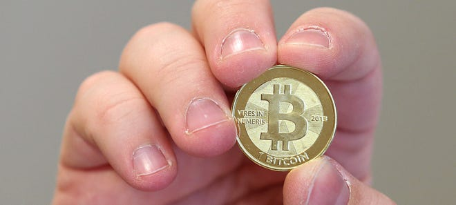 Software engineer Mike Caldwell shows the front of a physical Bitcoin he minted in his shop on April 26, 2013, in Sandy, Utah.