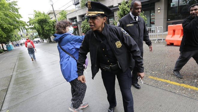 Seattle Police Chief Carmen Best bumps elbows with a protesters as she leaves after speaking with demonstrators near a closed Seattle police precinct Tuesday in Seattle.