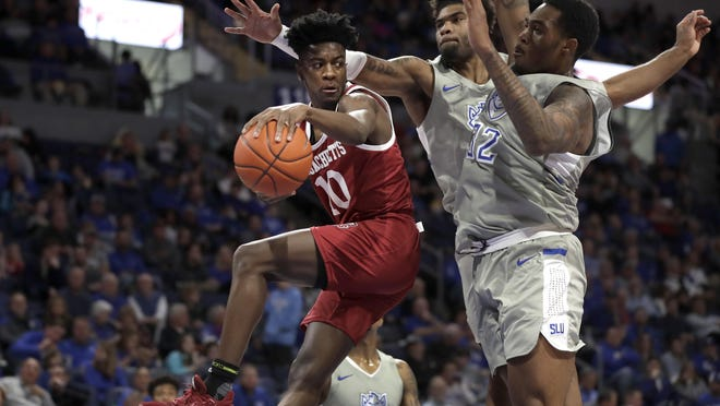 Massachusetts' Sean East II (10) passes around Saint Louis' Jimmy Bell Jr., right, and Hasahn French in an Atlantic 10 game last season. East's transfer waiver to Bradley was approved Tuesday.