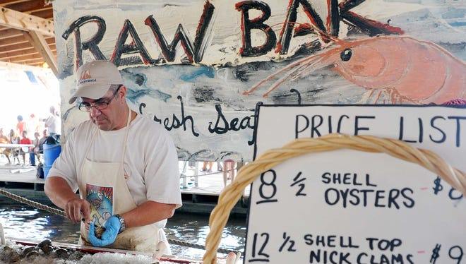 Mike Fardone of Stow Creek shucks oysters during Bay Day in 2013.