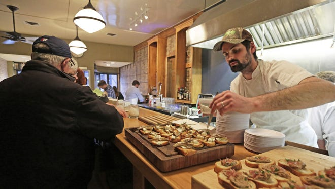 Owner/chef Jon Horan puts the finishing touches on appetizers as Town Council Kitchen & Bar in Neenah welcomes guests during a preopening event.