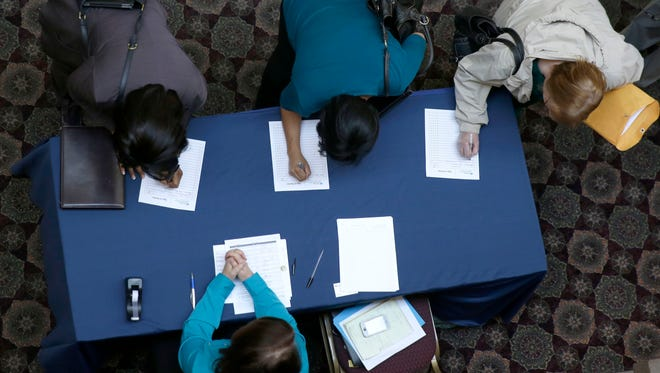 Job seekers sign in before meeting prospective employers during a career fair at a hotel in Dallas.