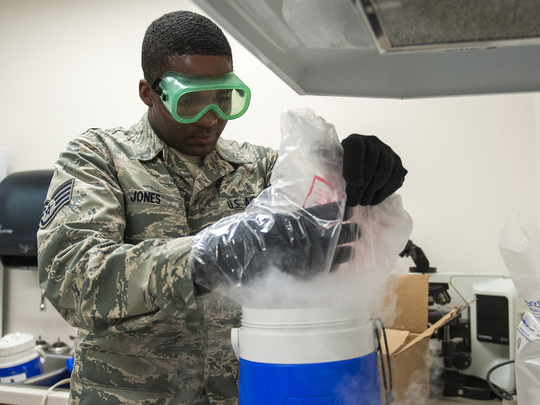 Staff Sgt. Derrick Jones, 96th Aerospace Medicine Squadron public health technician, drops dry ice into the carbon dioxide cooler July 20 at Eglin Air Force Base, Fla. The cooler emits carbon dioxide and is hung next to the traps to lure the mosquitos in. Mosquitoes are attracted to the carbon dioxide that mammals exhale.