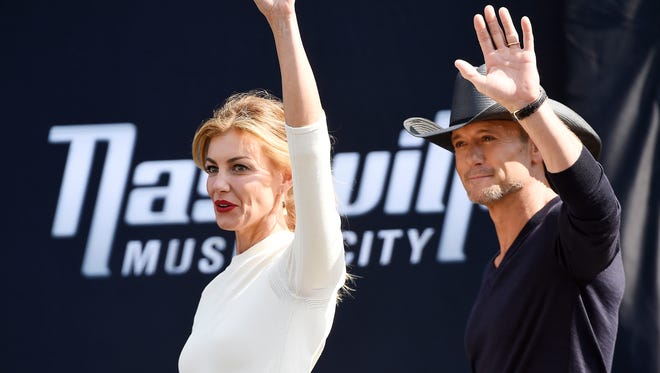 Faith Hill and Tim McGraw  wave to fans as the step on the stage.A big week got even bigger for Faith Hill and Tim McGraw on Wednesday, as the superstar country couple received their own stars on NashvilleÕs Music City Walk of Fame.Hill and McGraw unveiled their stars in the pavement at Walk of Fame Park Wednesday morning, as an audience of family, friends, and hundreds of fans cheered them on. Wednesday Oct. 5, 2016, in Nashville, Tenn.