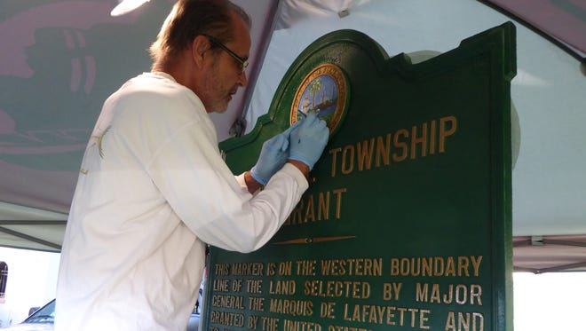 Artist Mick Slager, a longtime Los Robles resident, works on the Lafayette Township Grant historic marker that has been returned to its original site outside the Los Robles neighborhood.