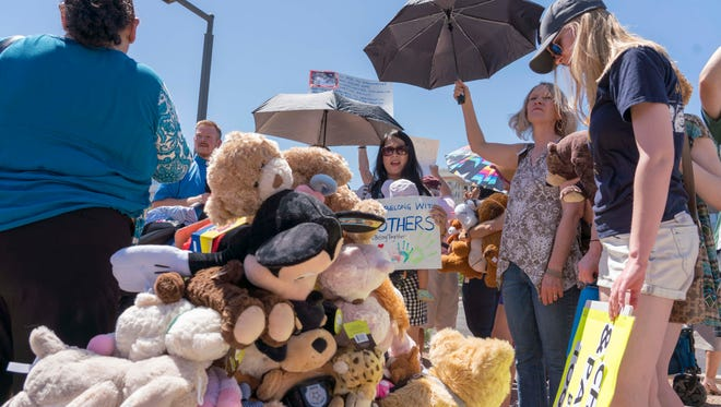 Migrant-rights supporters bring stuffed toys for children who are in DHS custody as protesters from both sides of the immigration debate rally outside the offices of Sens. John McCain and Jeff Flake in Phoenix on June 20, 2018.