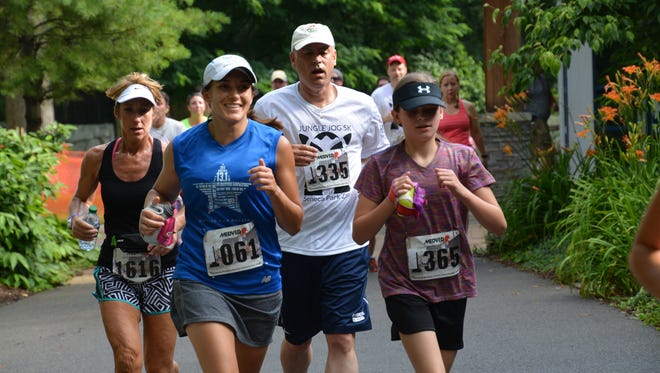 Runners sprint through the Seneca Park zoo during the Jungle Jog 5K.