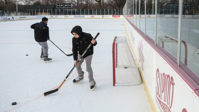 Ivan Tejeda, 13, of Detroit and Jonathon Galindez, 12, of Detroit play ice hockey at a rink in Clark Park in Detroit on Wednesday, December 28, 2016.