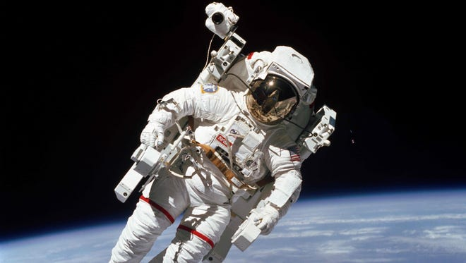 "This photo taken on February 7, 1984, shows the first untethered spacewalk, NASA astronaut Bruce McCandless is in the midst of the first ""field"" tryout of a nitrogen-propelled backpack device called the Manned Maneuvering Unit (MMU)."
