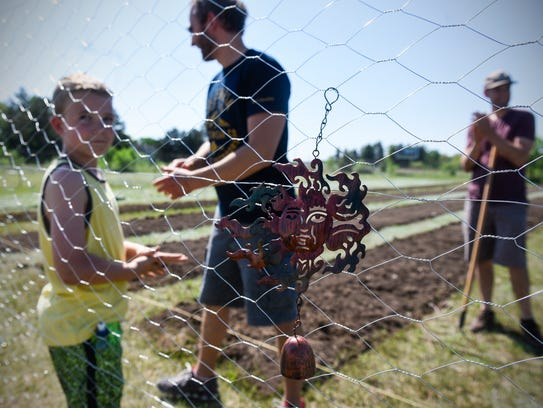 People volunteer at a community garden for area refugees
