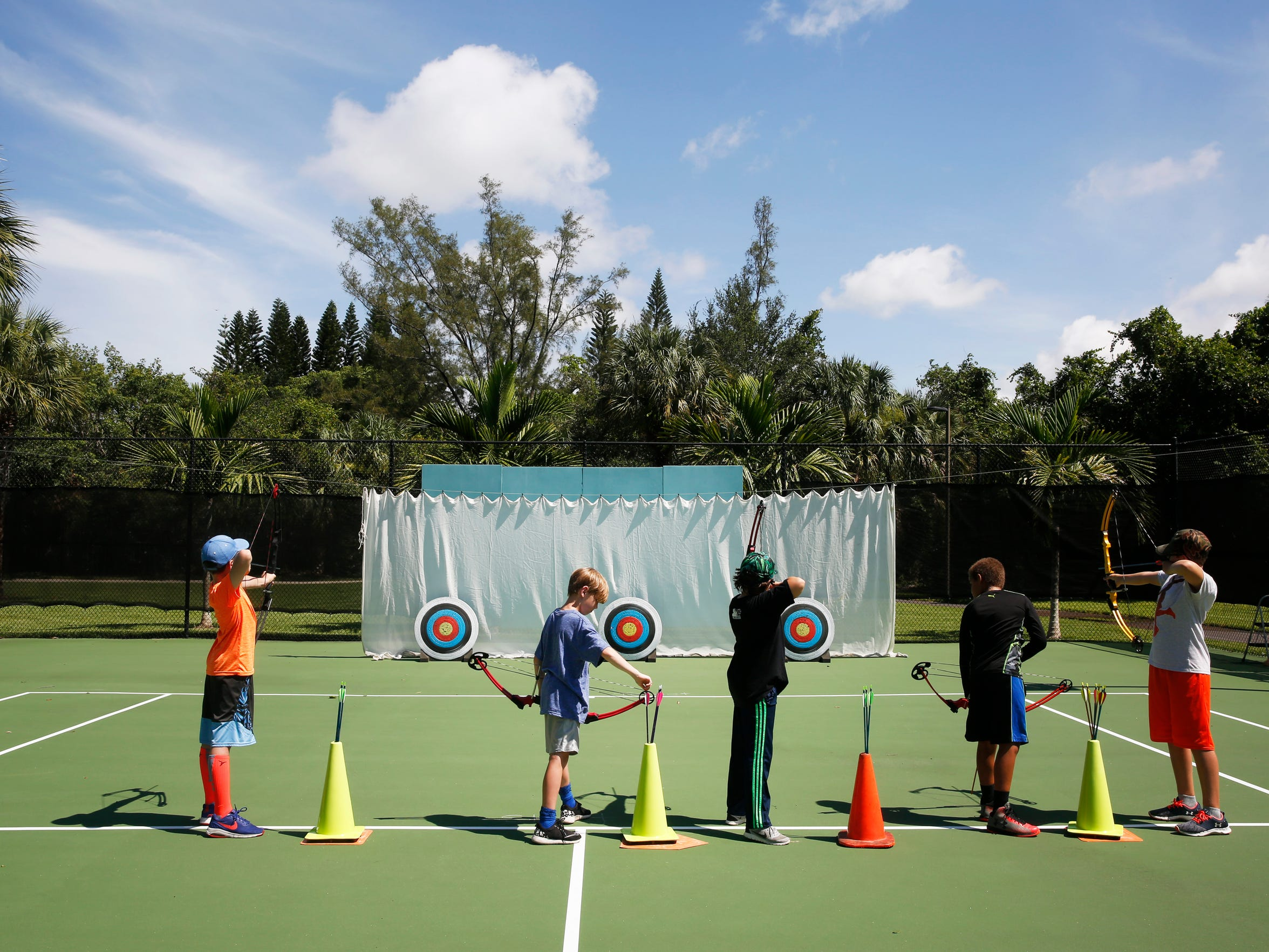 Campers take aim at targets during an archery lesson on the tennis courts at Anthony Park on Wednesday, Aug. 2, 2017.