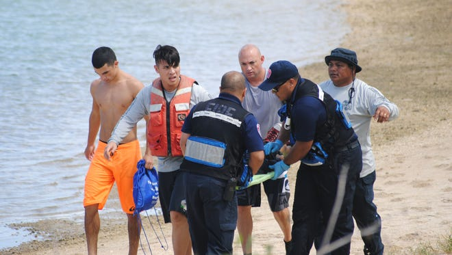 Medics from the Guam Fire Department, assisted by other beachgoers, rush 10-year-old Jetrick Tom to a nearby ambulance. Jetrick, 10 and his brother Jemphil, 11, drowned at Adelup beach on Sunday.