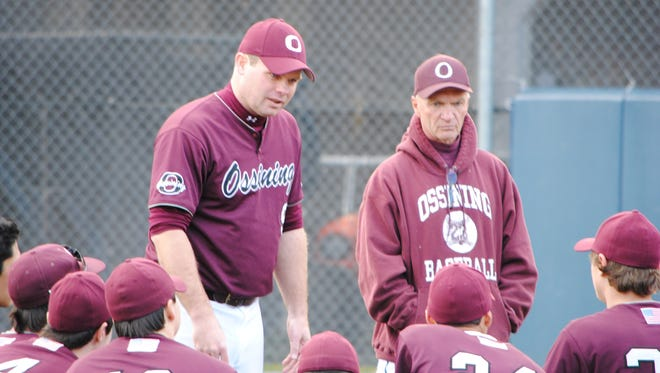 Ossining baseball coach Bill Casey (standing, left) speaks with his team.