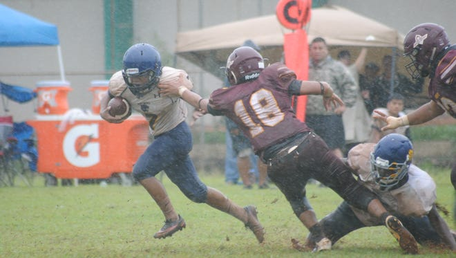 Guam High School Panthers Tyrone Rosario, No. 7, evades the outstretched hand of the FD Friars' Isiah Reyes during their high school football game Saturday at the UOG field. FD beat the Panthers 30-0.